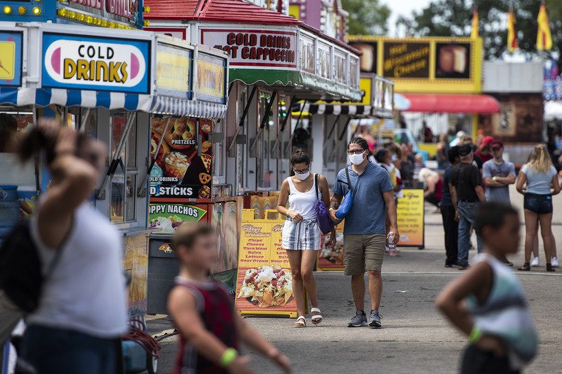 Two people in masks walk in a crowded area of the fair near food vendors