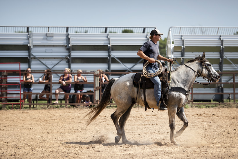 A man riding a horse holds a rope as he rides on a dirt arena