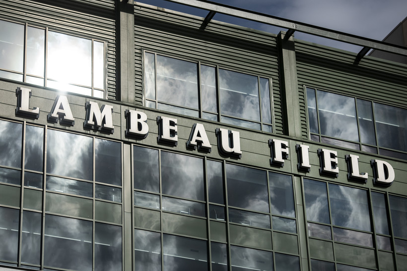 Clouds and a sunny sky reflect in windows on the side of Lambeau Field