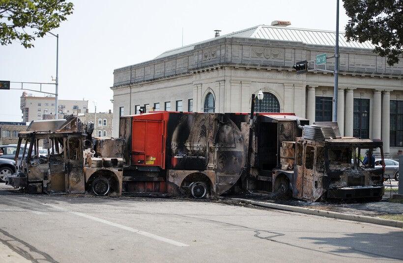 large burned up trucks block the road