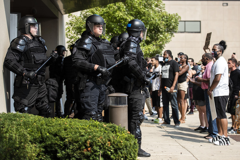 police in riot gear stand with batons next to protesters