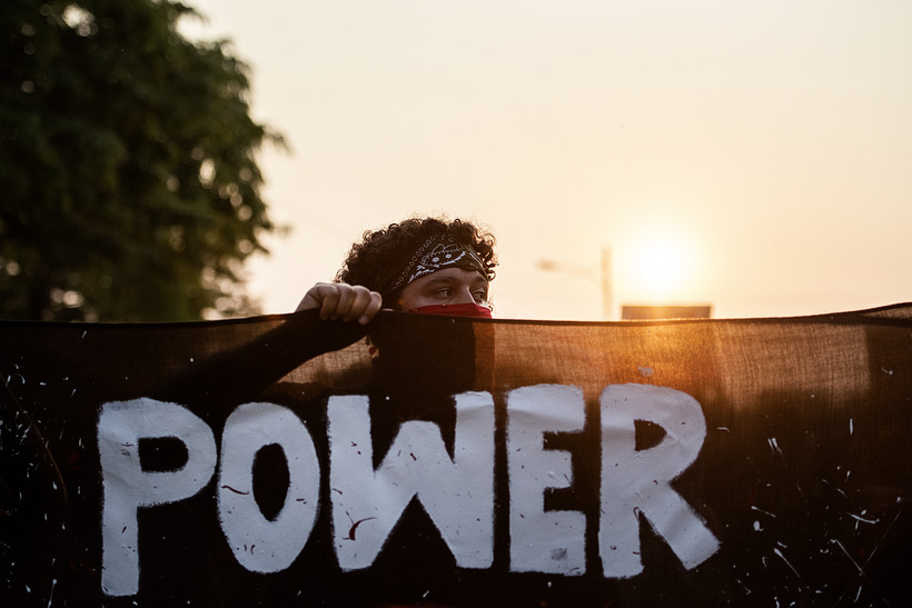 """A protester holds a banner with the word """"power"""" as the sun sets behind him"""