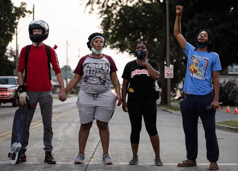 four people hold hands and raise their fists as they stand in the road