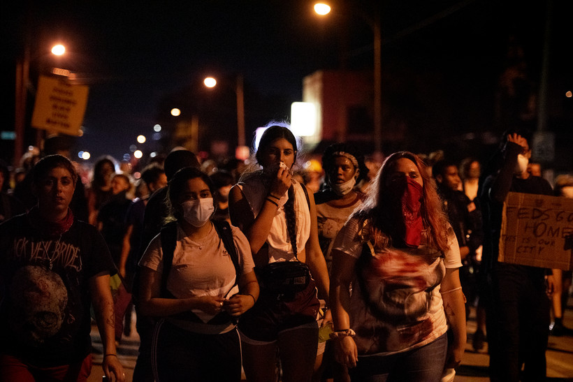 protesters march on a dark street illuminated by street lights