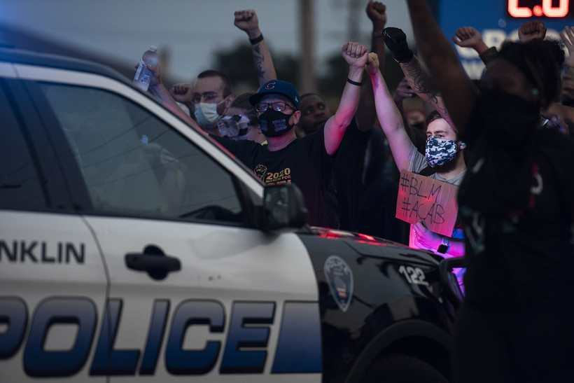 Protesters are illuminated by police lights as they raise their fists