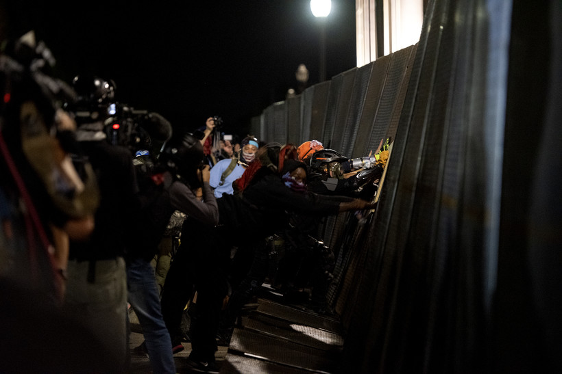 a large black fence bends slightly as protesters push on it