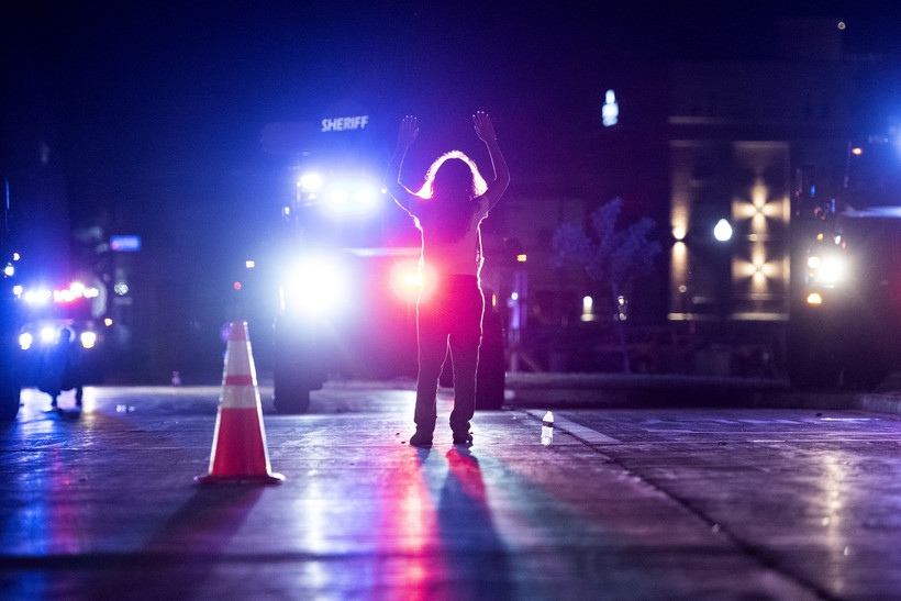 blue and red lights fill the night as a lone protester raises their arms in front of large law enforcement vehicles