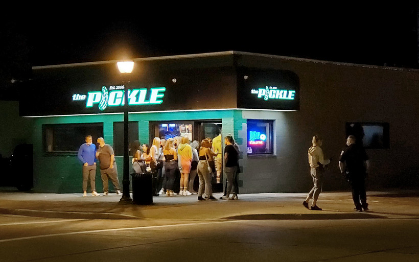 "Illuminated by a street light, a crowd of people gather in the doorway of a bar called ""The Pickle"""