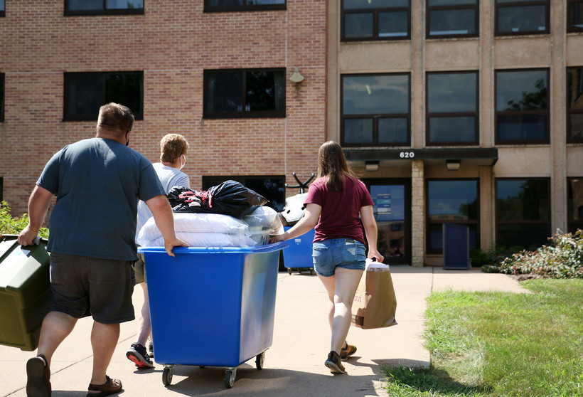 Three people move a large blue rolling container into a residence hall