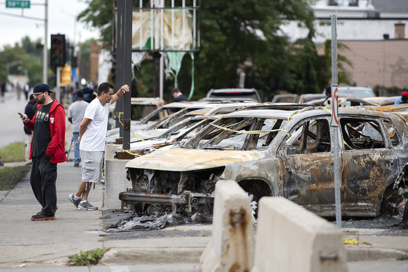 people stand on the sidewalk next to burned cars at a car dealership