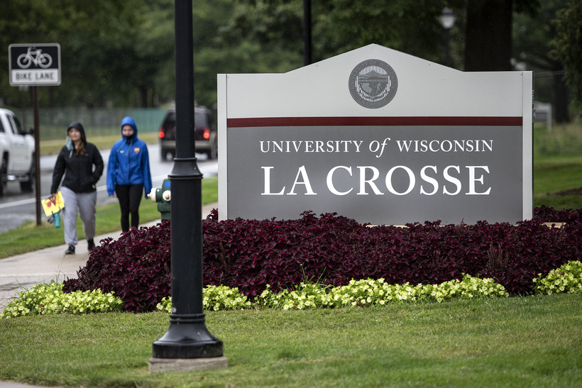 """People walk by a sign that says """"University of Wisconsin La Crosse"""""""