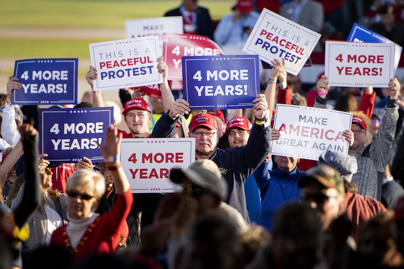 "People hold signs that say ""4 more years"" and ""peaceful protest"" in a crowd"