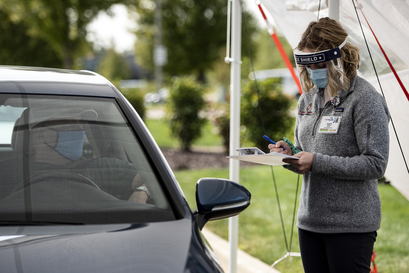 a woman in a mask and face shield writes on a clip board while standing under a white tent outside set up for the drive thru service