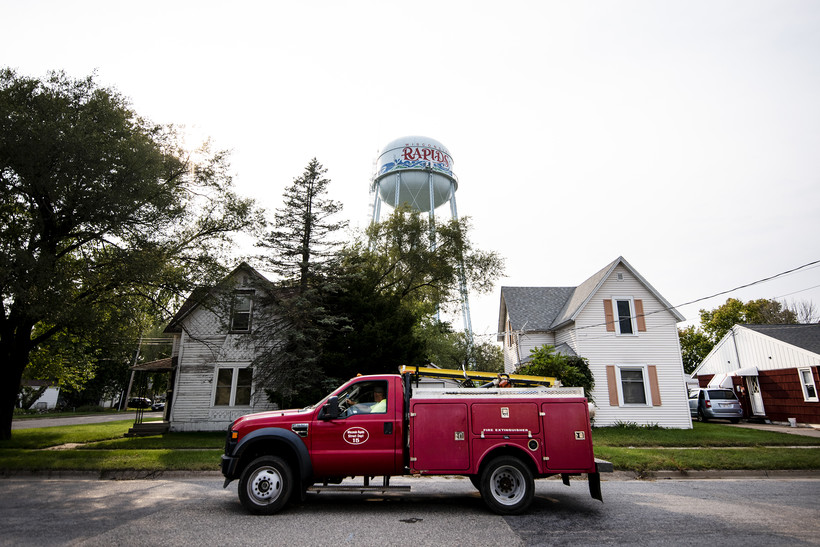 """a bright red truck passes by two homes and a water tower that says """"Wisconsin Rapids"""""""
