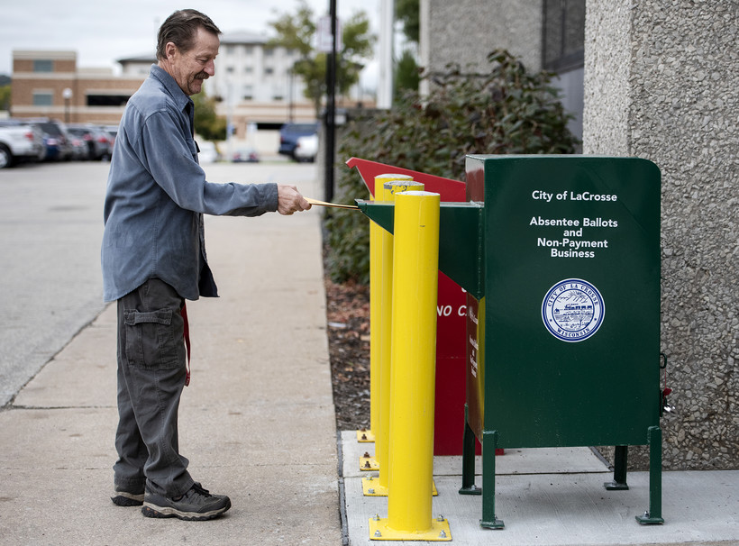 A man places a ballot in a yellow envelope into a green drop off box that resembles a public mail box.