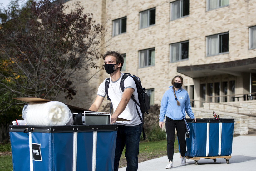 A student in a face mask rolls a blue bin filled with belongings