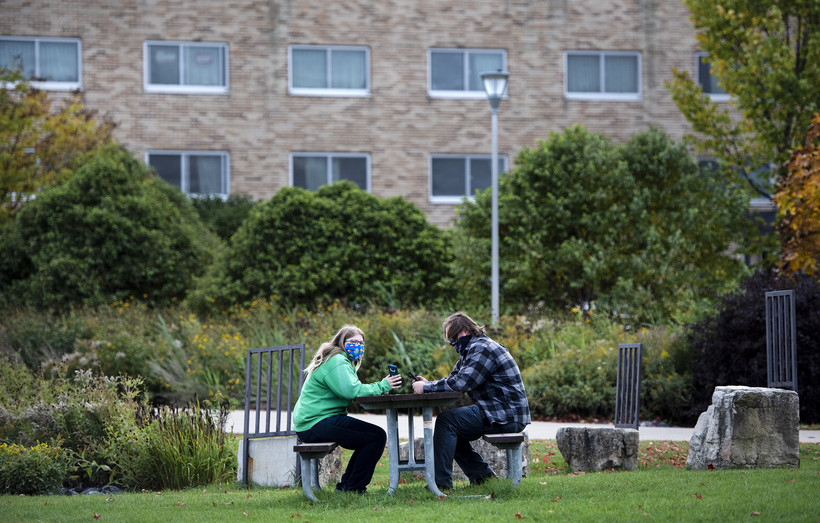 two people sit at a picnic table outdoors. a residence hall can be seen in the background.