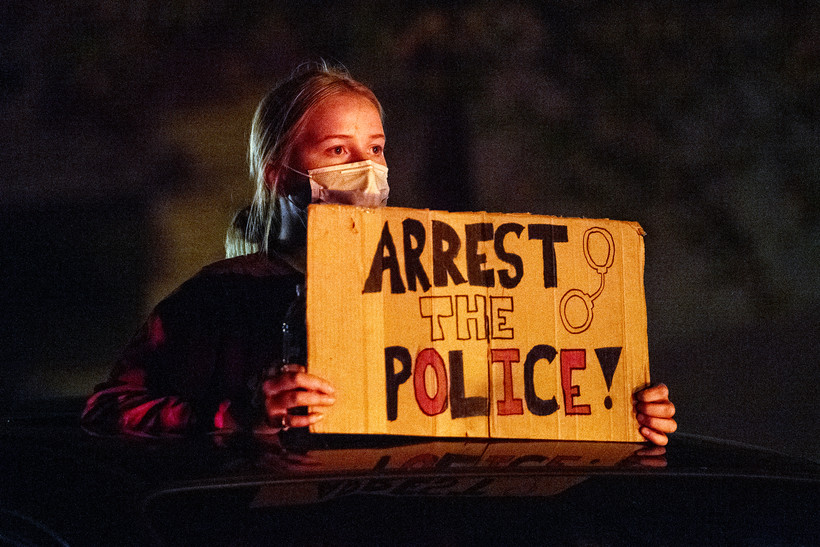 "A protester holds a sign that says ""arrest the police."" She's is lit by a red tail light in an otherwise dark night."