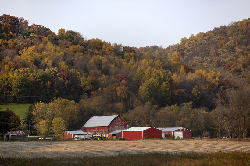 Hills with fall colors surround a red barn