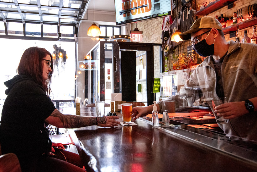 a bar tender in a mask puts a beer on the table for a customer