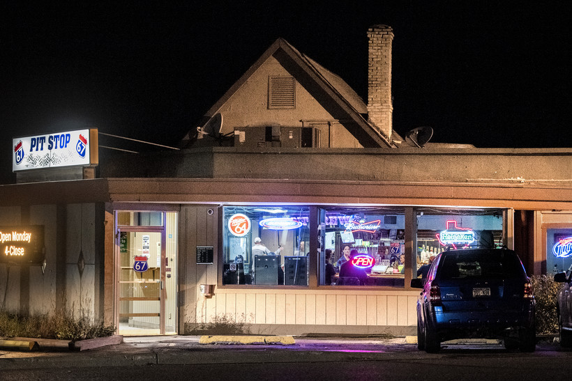 cars are parked outside of a bar at nighttime. neon signs light up the windows.