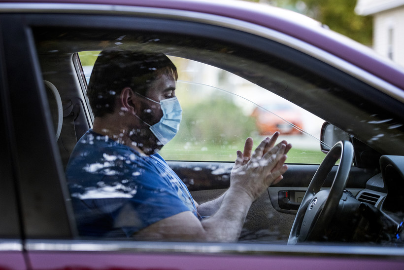 A man sits in his car and rubs hand sanitizer on his hands