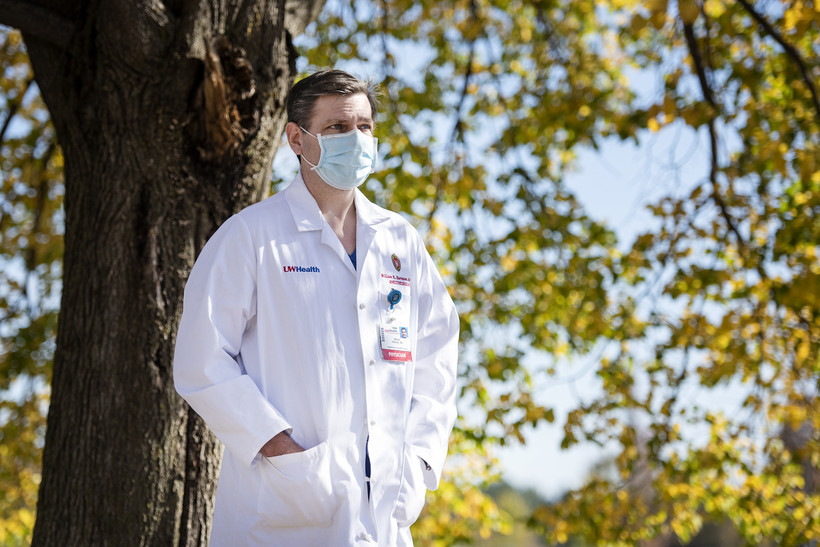 A doctor in a white coat and face mask stands in front of a tree with yellow fall leaves