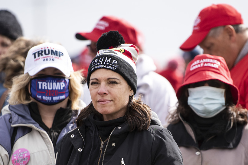 A woman in a Trump hat and no face mask stands in line next to two supporters in masks
