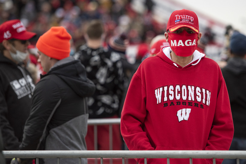"""A Trump supporter in a Wisconsin Badgers hoodie, a Trump hat, and a face mask that says """"MAGA"""""""
