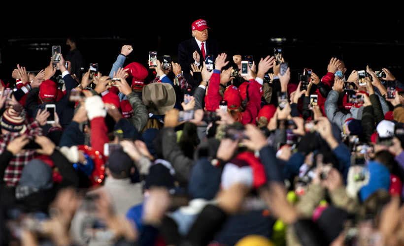 President Donald Trump wears a red hat as he approaches supporters who are gathered close together and raising their hands