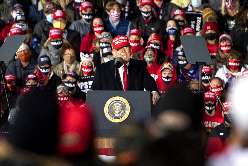 President Donald Trump stands on stage wearing a red MAGA hat as he speaks to supporters