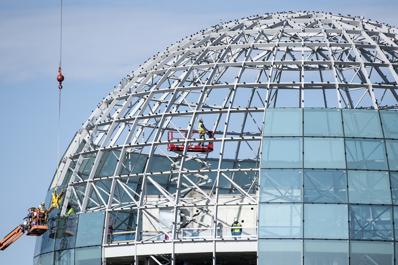 A worker in a lift looks up as he works inside a large globe.