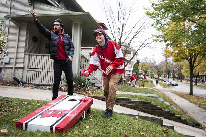 two students throw bags outdoors on a lawn