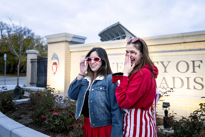 girls stand in front of a sign at Camp Randall in badgers gear and sunglasses