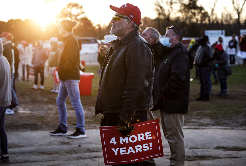 "The sun sets as a Trump supporter holds a sign that says ""4 MORE YEARS!"""