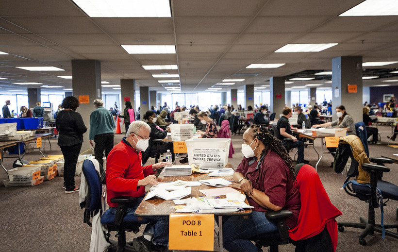 workers at tables sort through ballots in a large room filled with other workers