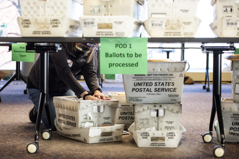 crates of ballots are on the floor and tables as a worker in a face shield flips through them with her hands