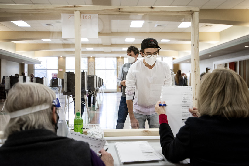 A voter in a white face mask looks through plexiglass as a poll worker holds up a ballot