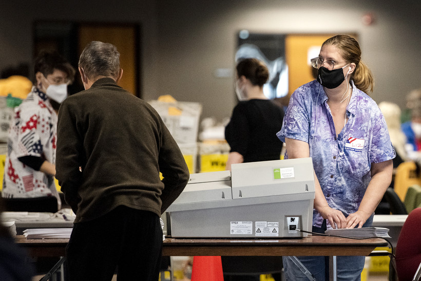 a woman in a face mask puts her hands on a stack of ballots