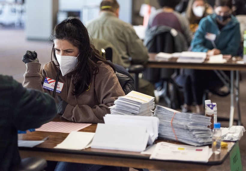 a woman in a white face mask looks down as she works at a table