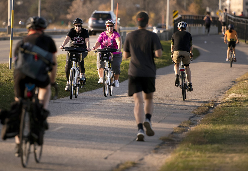 two women on bikes on a sidewalk as others bike and run in the opposite direction