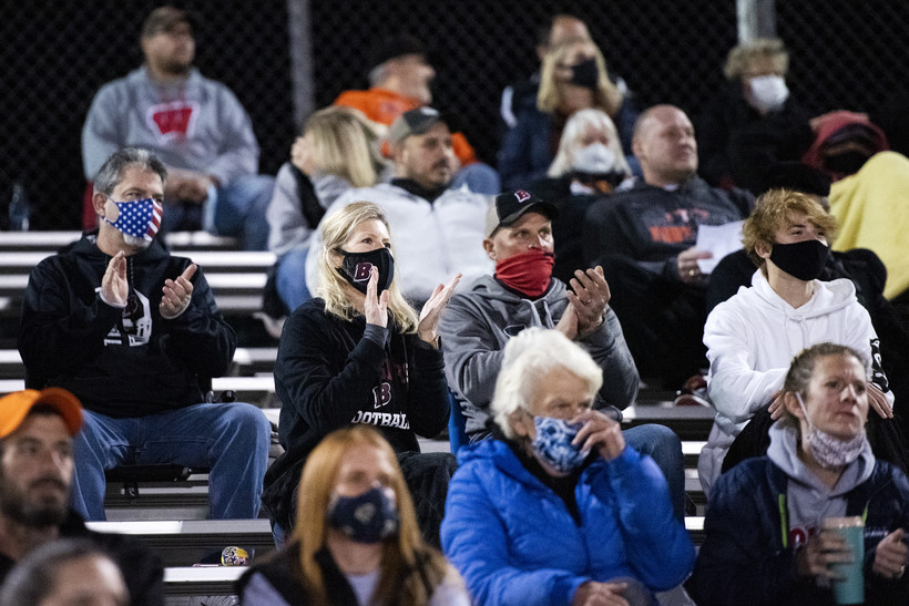 fans in face masks applaud from the bleachers