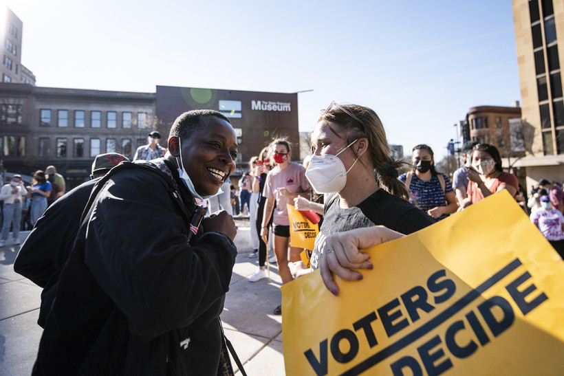 """a person holds a sign that says """"voters decide"""" as she dances with another Biden supporter"""