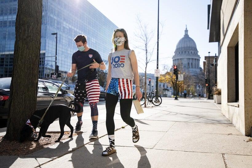 "two people in U.S. flag printed shorts walk a dog. a woman wears a ""Joe 2020"" shirt."