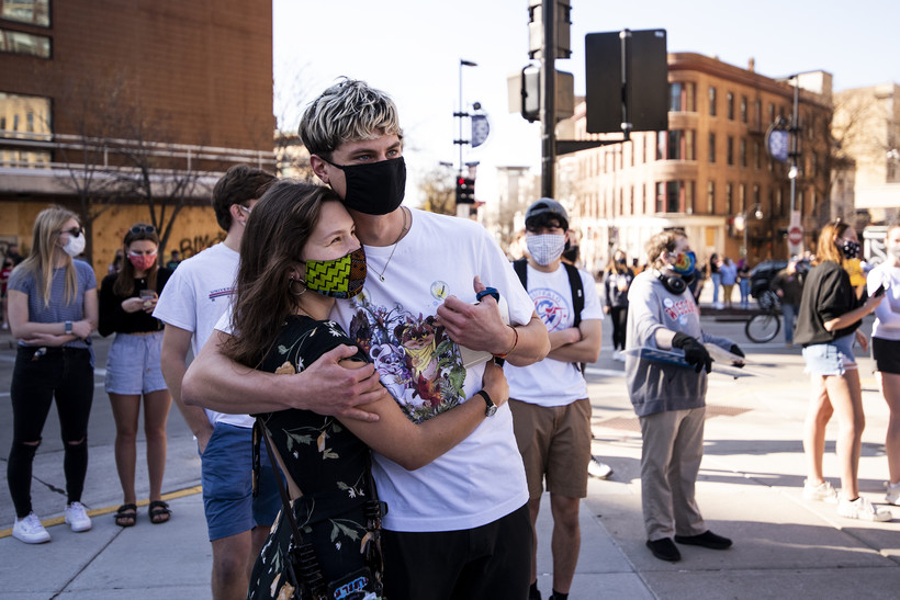 two people in face masks hug at a rally outside the Wisconsin State Capitol
