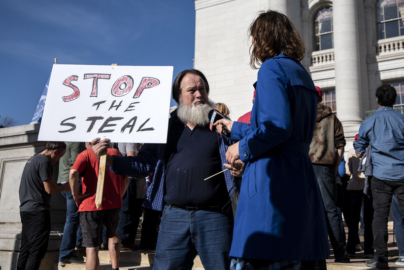 """A man holds a sign that says """"stop the steal"""""""