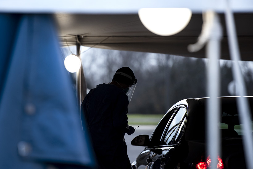 A man in a face mask holds a swab as he approaches the driver of a vehicle. The man is in silhouette and under a tent as the sun begins to set.