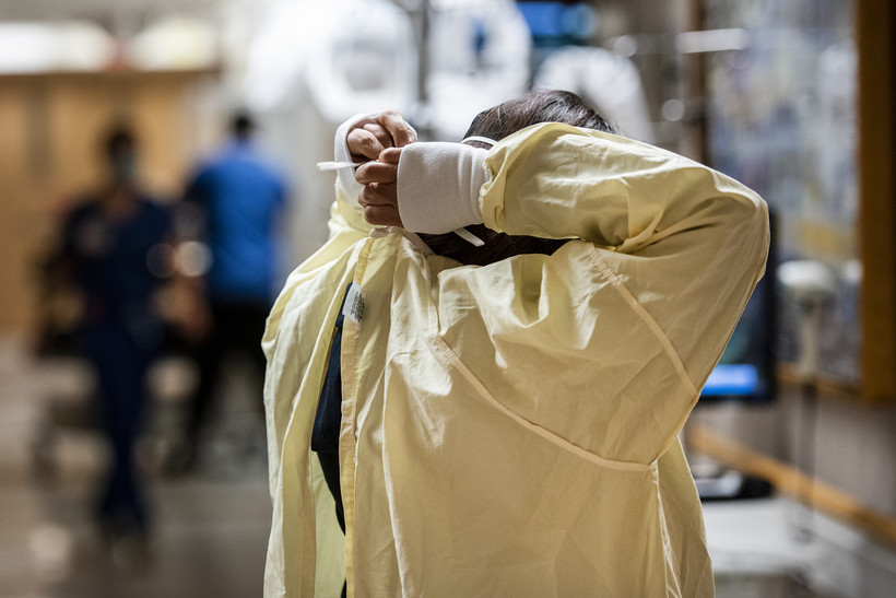 A woman can be seen reaching behind her head to tie up a yellow medical gown