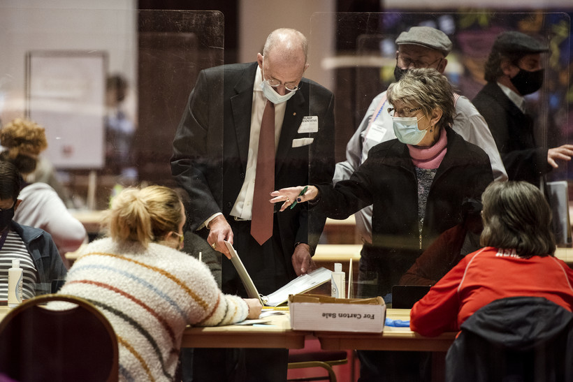 Two people look in a binder and gesture as the recount goes on