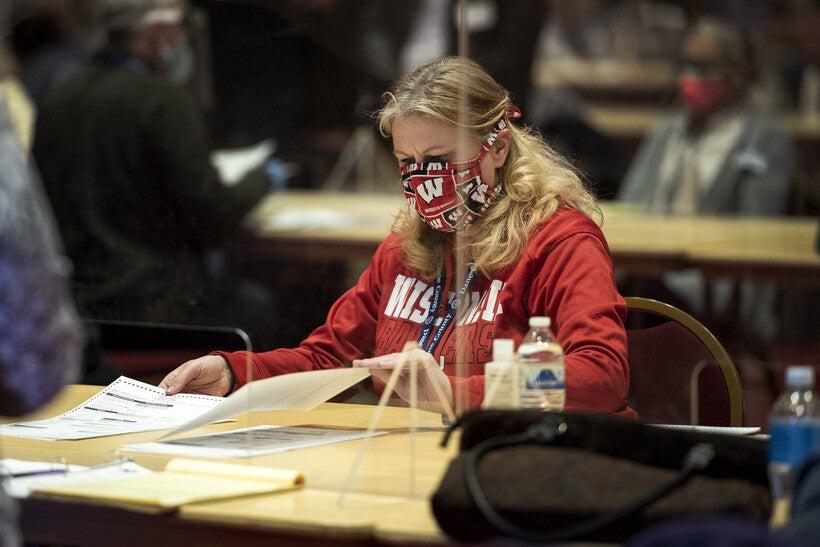 A woman sits behind plexiglass and flips through ballots